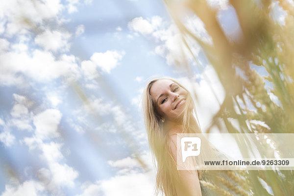Porträt einer lächelnden jungen Frau auf einem Roggenfeld
