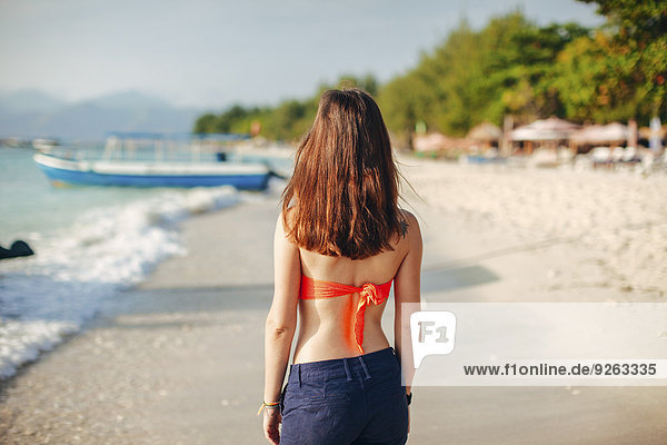 Indonesien  Gili Inseln  Frau am Strand stehend  Rückansicht