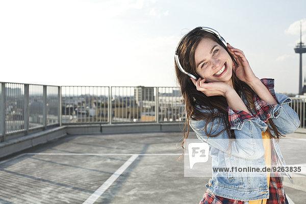 Deutschland  Nordrhein-Westfalen  Köln  Portrait einer lachenden jungen Frau beim Musikhören mit Kopfhörern