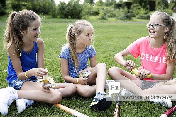 Three girls sitting on a meadow having a break