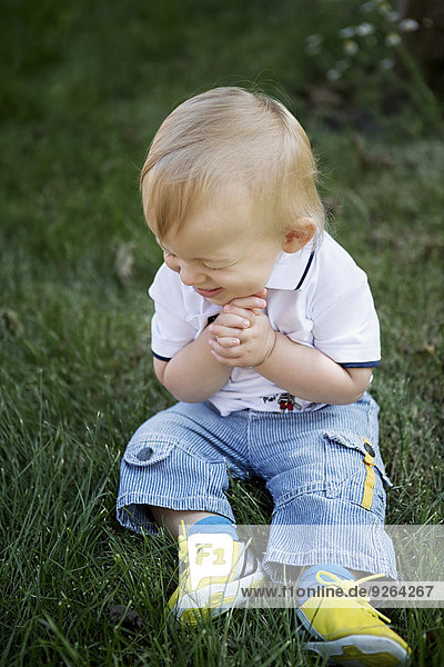Germany  Oberhausen  Blond baby boy sitting on grass in park
