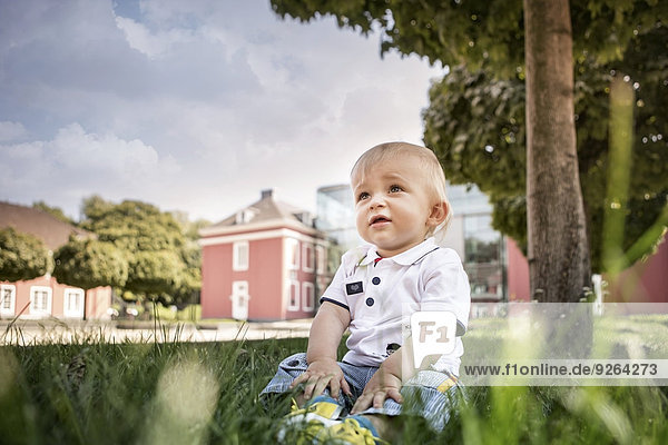 Germany  Oberhausen  Blond baby boy sitting in park of Oberhausen Castle