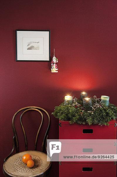 Adventskranz auf Sideboard an roter Wand