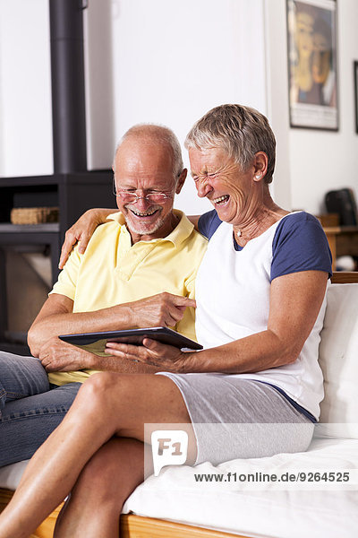 Seniorenpaar sitzt auf der Couch und hat Spaß mit digitalem Tablett