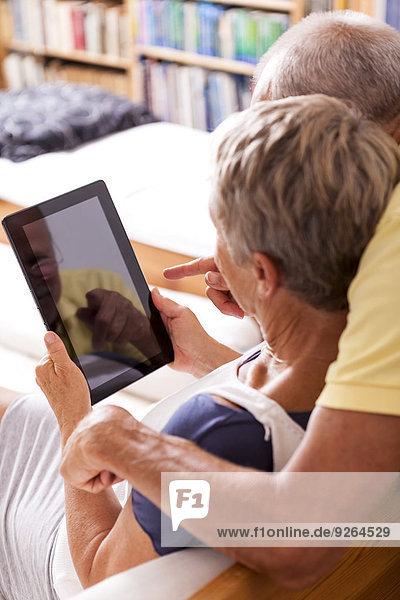 Seniorenpaar auf Couch sitzend mit digitalem Tablett  Teilansicht