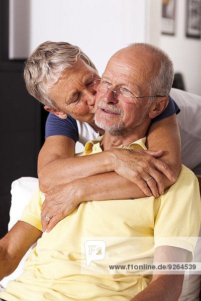 Seniorin  die ihren Mann umarmt und küsst.