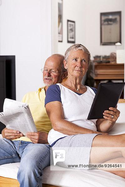 Seniorenpaar sitzt auf der Couch und liest Zeitung mit digitalem Tablett.