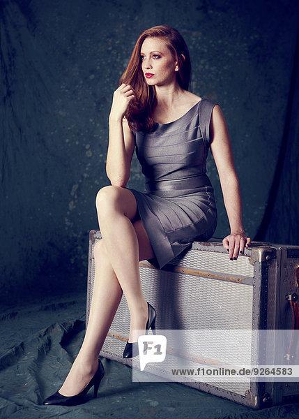 Porträt einer gut gekleideten Frau  die auf einem alten Koffer sitzt.