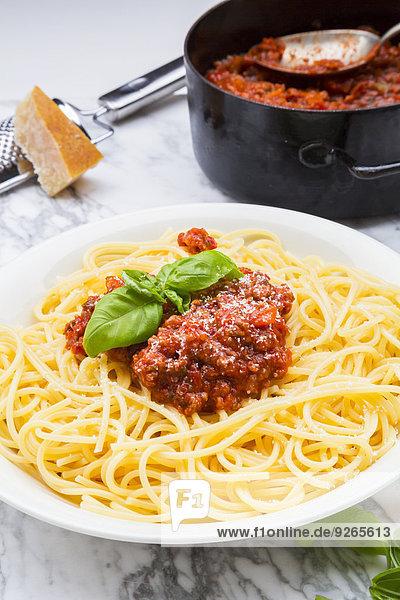 Teller Spaghetti Bolognese verziert mit Basilikumblättern auf weißem Marmor