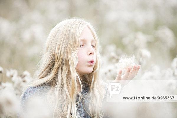 Porträt eines Mädchens  das auf einem Feld steht und Samen aus der Hand bläst.