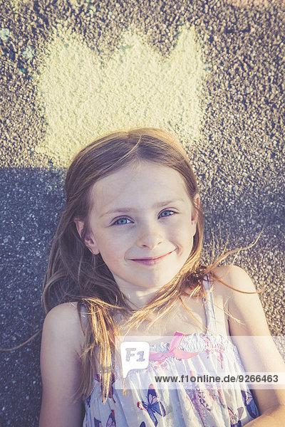 Porträt eines lächelnden Mädchens auf Asphalt mit bemalter Krone Porträt eines lächelnden Mädchens auf Asphalt mit bemalter Krone