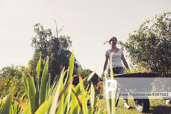 Reife Frau schiebt Schubkarre im Garten