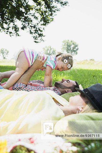 Junges Paar und kleine Tochter entspannen in der Natur