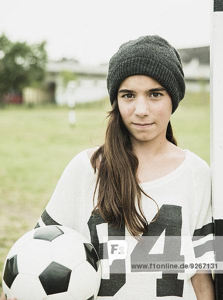 Porträt eines Teenagermädchens mit Fussball am Torpfosten