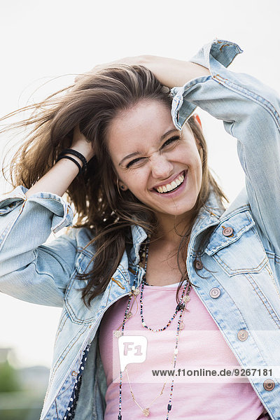 Portrait of laughing teenage girl with hands in her hair