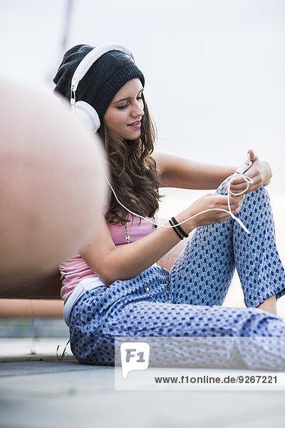 Portrait of teenage girl holding smartphone hearing music with headphones