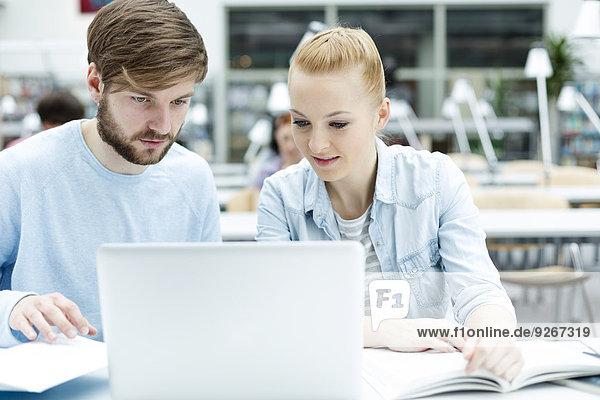 Studenten in einer Universitätsbibliothek mit Laptop
