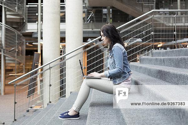 Junge Frau mit Laptop auf der Treppe