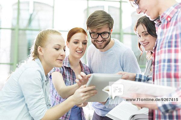 Studierende in einer Universitätsbibliothek mit digitalem Tablett