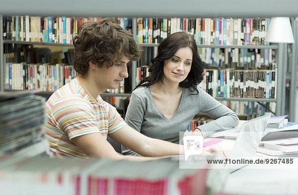 Zwei Studenten in einer Universitätsbibliothek mit Laptop