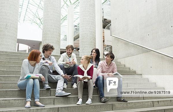 Studentengruppe mit Büchern auf der Treppe sitzend