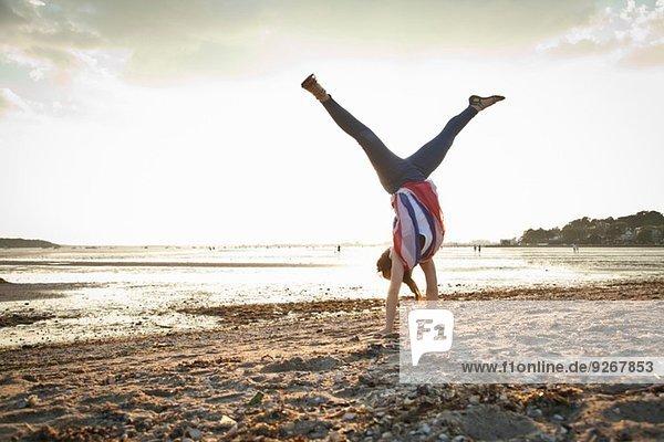 Junge Frau beim Handstand am Strand von Bournemouth  Dorset  UK