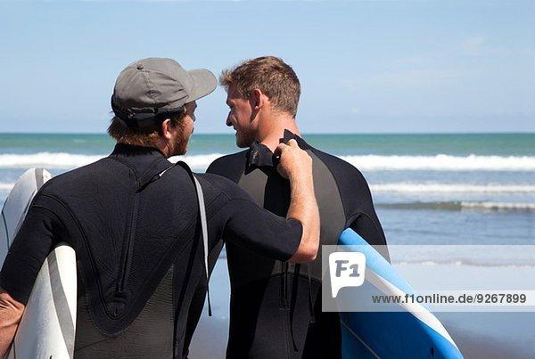 Rückansicht des männlichen Surfers beim Überprüfen des Neoprenanzug-Reißverschlusses seiner Freunde