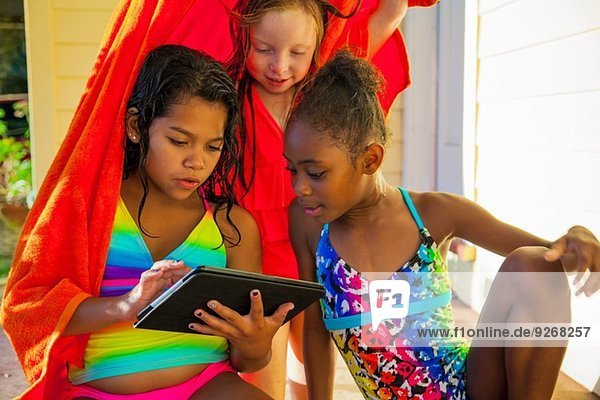 Three girls wrapped in towel on porch looking at digital tablet