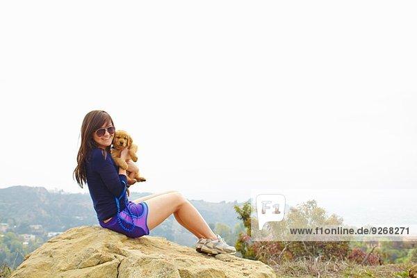 Junge Frau sitzt auf einem Felsen und hält einen Labrador-Welpen.