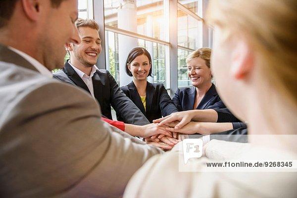Über Schulteransicht einer Gruppe von Geschäftsfrauen und Männern  die mit den Händen im Kreis lächeln.