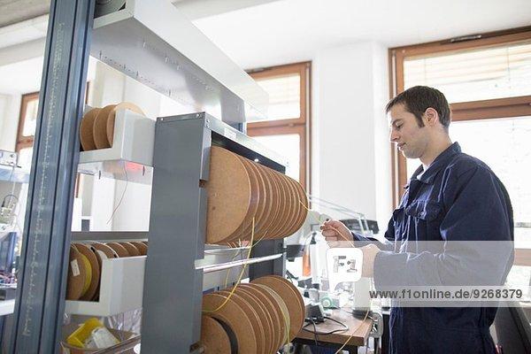 Elektriker zieht Stromkabel von der Kabeltrommel in der Werkstatt
