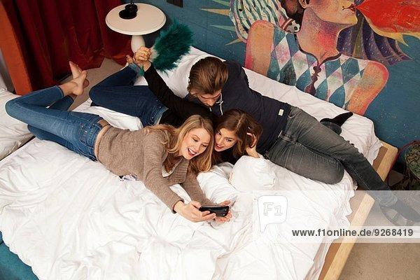 Drei erwachsene Freunde liegen auf dem Hotelbett und nehmen Selfie auf dem Smartphone.