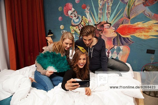 Three adult friends on hotel bed taking selfie on smartphone