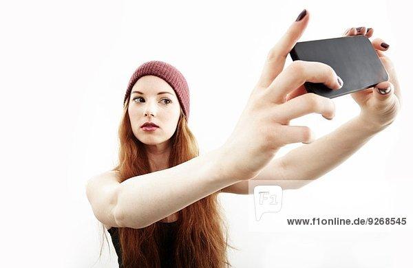 Studio-Porträt einer jungen Frau  die auf dem Smartphone Selfie macht