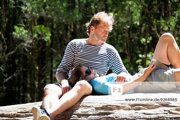 Pärchen entspannen auf einem Waldbaumstamm im Sonnenlicht