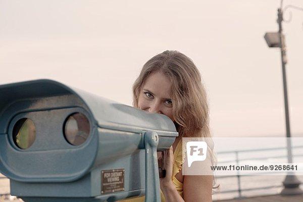 Junge Frau versteckt sich hinter einem Münzfernglas am Santa Monica Pier  Kalifornien  USA