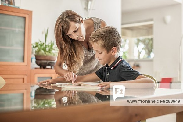 Mutter und Sohn bei den Hausaufgaben am Esstisch