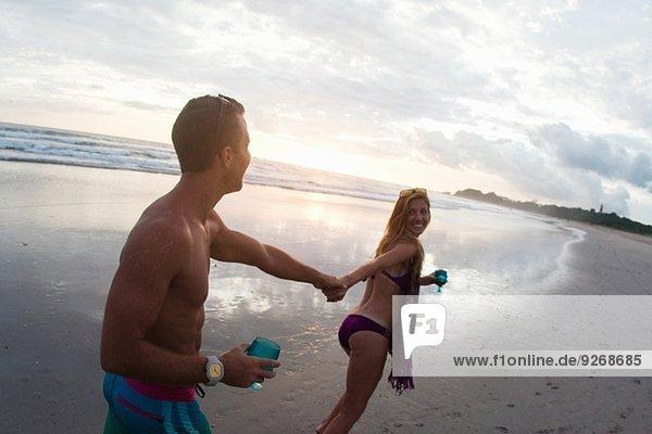 Mittlere erwachsene Frau führt Freund von Hand am Strand  Nosara  Guanacaste  Costa Rica