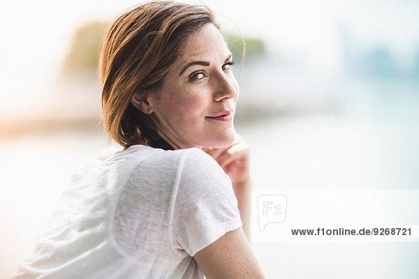 Porträt einer erwachsenen Frau  die über die Schulter schaut.