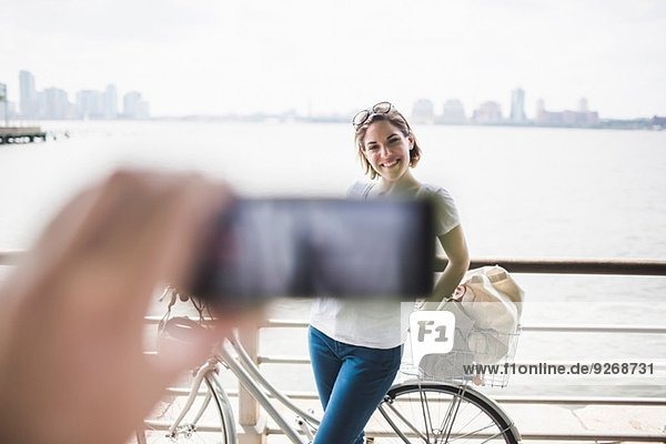 Männliche Hand fotografiert Freundin mit Smartphone am Flussufer  New York City  USA Männliche Hand fotografiert Freundin mit Smartphone am Flussufer, New York City, USA