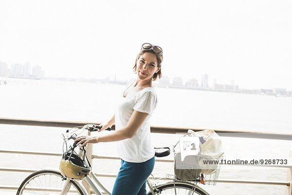 Portrait einer erwachsenen Radfahrerin am Flussufer  New York City  USA