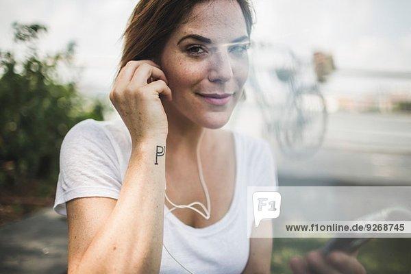 Porträt einer erwachsenen Frau  die Kopfhörer hört