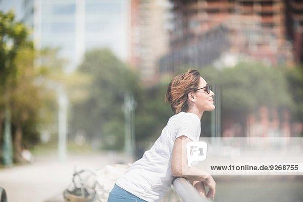 Lächelnde mittlere erwachsene Frau  die sich auf Stadtgeländer stützt. Lächelnde mittlere erwachsene Frau, die sich auf Stadtgeländer stützt.