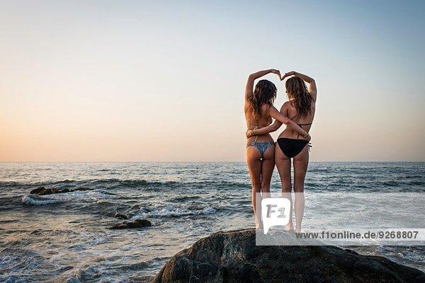 Zwei junge Frauen auf Felsen im Meer  Rückansicht