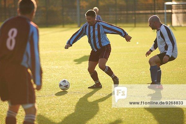 Fußballspieler  die dem Ball nachlaufen