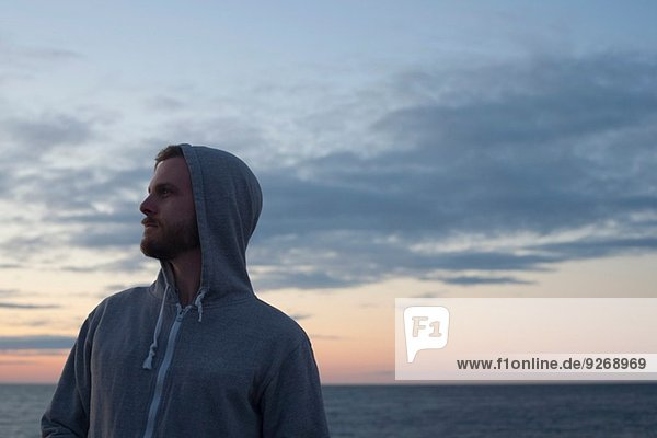 Mittelgroßer Mann mit Kapuze und Blick über die Schulter auf die Küste  Gloucester  Massachusetts  USA