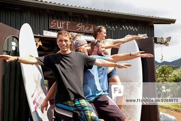 Gruppenporträt von fünf jungen erwachsenen Surferfreunden  die mit ausgestreckten Armen posieren