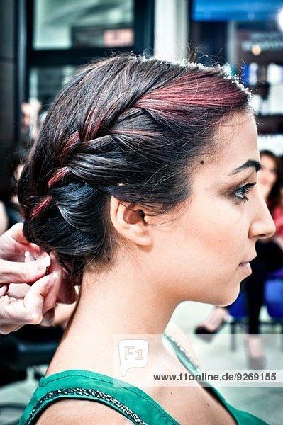 Friseurin flechtend junge Frau im Friseursalon