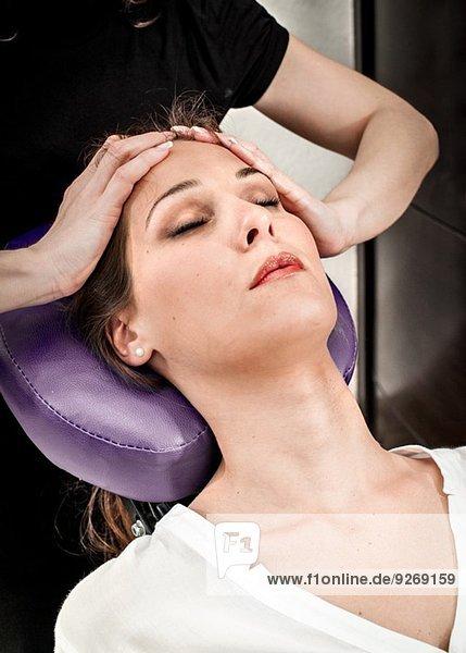 Masseurin  die die Stirn einer jungen Frau im Schönheitssalon massiert.