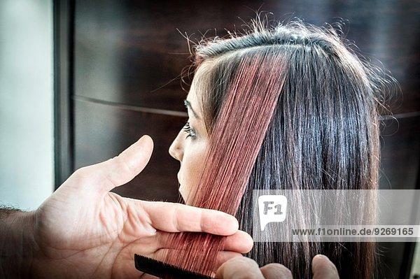 Friseur  der das Haar einer jungen Frau im Friseursalon kämmt.